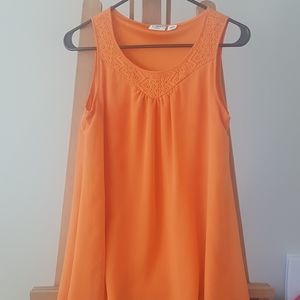 Girl's bright orange sleeveless shirt.